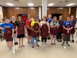 Culinary Arts students gather with their custom aprons for a group photo int he MSB student center