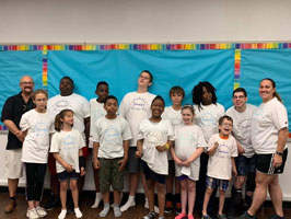 Summer Shape Up campers and staff gather in their custom t-shirts for a group photo in the MSB PE classroom