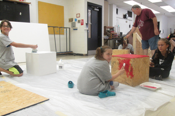 Broadway studetns decorate stes and props for the musical performance