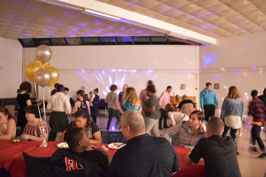 Photo of students dancing in the background and socialing at tables in the foreground. The large room the photo is taken in is decorated with balloons and bright party lights.